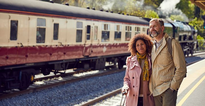 Bath Station, Bath, England. A steam train, the Royal Scot in steam with carriages on the rails. A couple, travellers, a man and woman standing on the platform.
