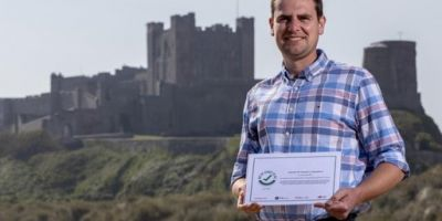 A man standing in front of Bamburgh Castle holding their 'We're Good To Go' certificate