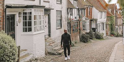 Man walking along a quiet country lane with cottages