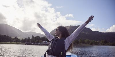 Woman with outstretched arms on a boat on the lake, Ullswater, Lake District, Cumbria.