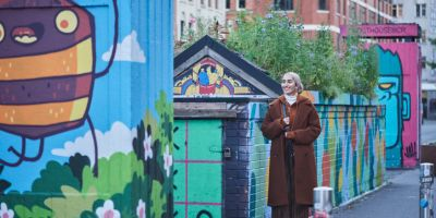 Woman walking past colourful murals on buildings near Stevenson Square, Manchester, England, UK.
