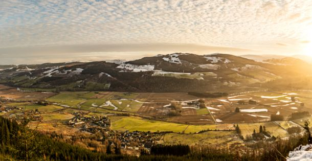 View over the highlands landscape, woodland and mountains with patches of snow in winter. Sun setting and a cloud pattern in the sky.