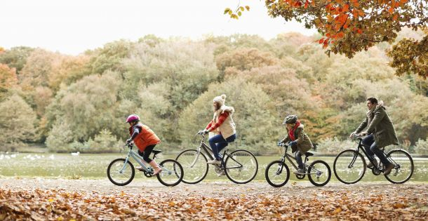 Family of fiour riding bikes in a park with autumn leaves