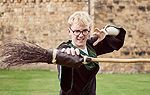 A boy dressed as harry potter holding a broomstick