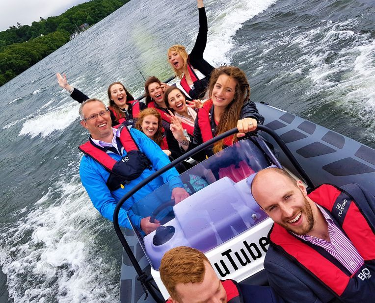 a group of people having fun on a speed boat on a lake