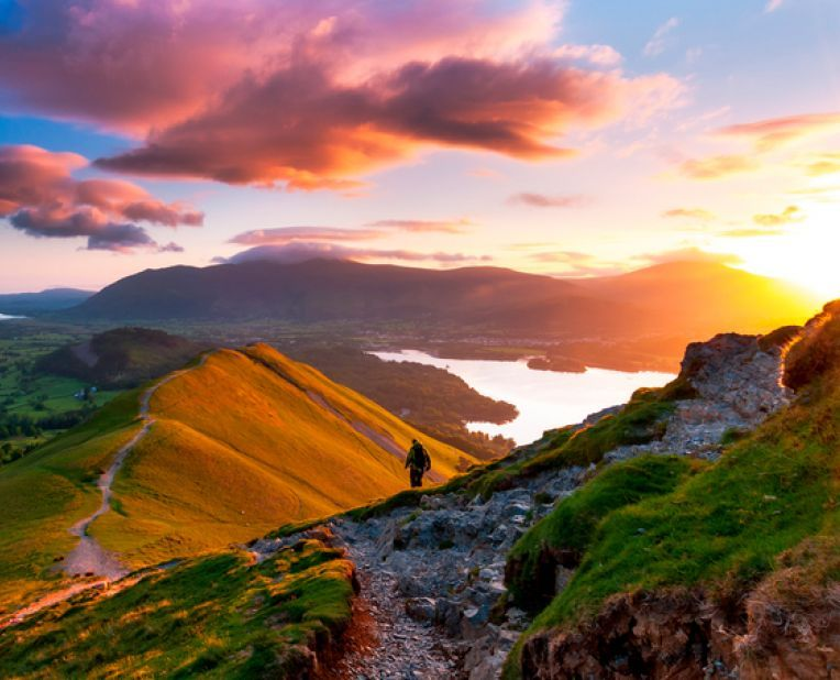 a walker overlooking a sunrise in the Cumbrian hills