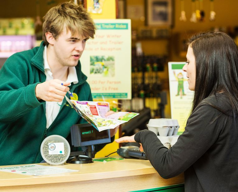a staff member showing a customer a map in an attraction shop