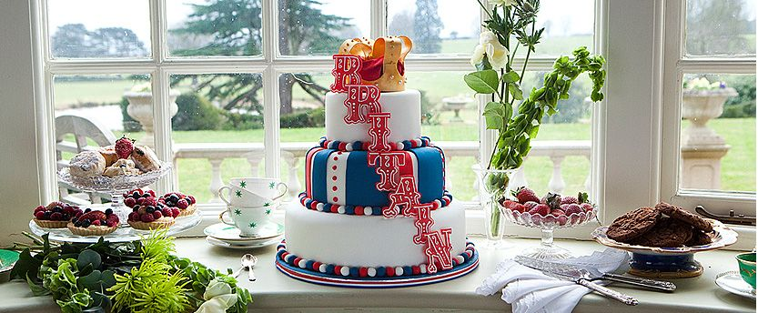 A decorated cake with Britain on it on a table in front of a pretty window