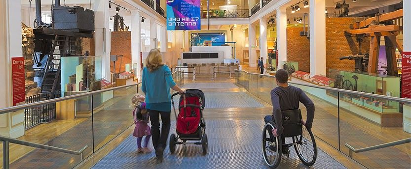 Man in wheelchair and woman with pram in a museum