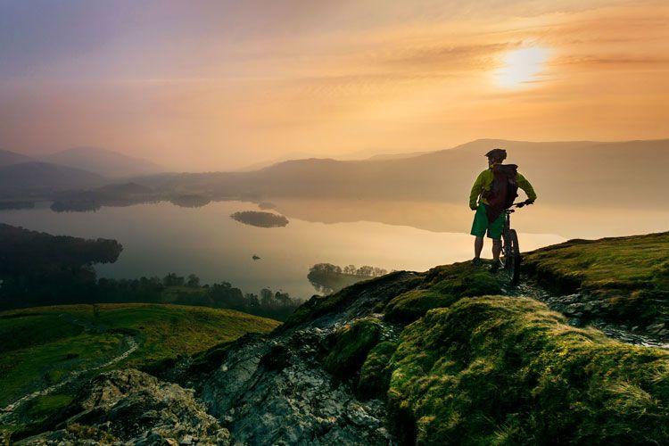 Mountainbiker kijkt uit over een van de meren van het Lake District in Engeland