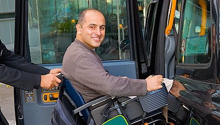 A man helping a smiling man in a wheelchair into a cab