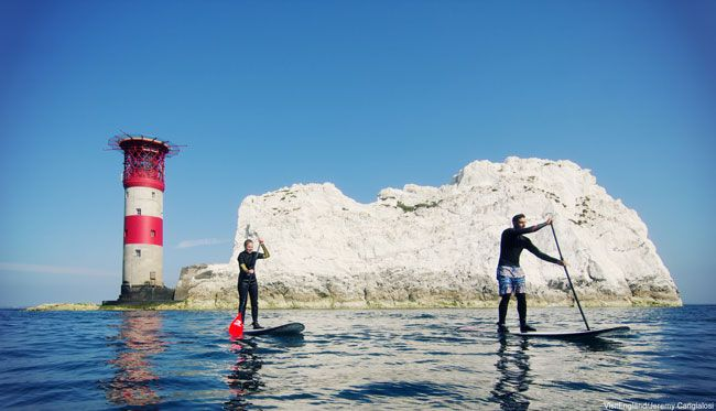 Two men paddle boarding at Alum Bay, Isle of Wight
