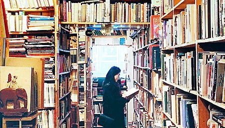 A woman stands reading a book in an interior view of Armchair Bookshop, Edinburgh, Scotland.