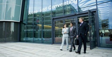 Three people in business suits leaving a convention centre together