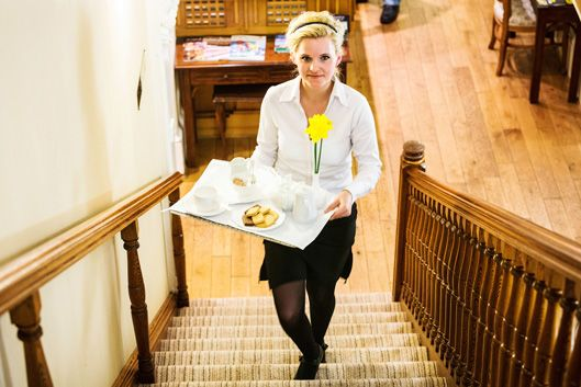 A young waitress walking up stairs carrying a breakfast tray (c) Alex Hare