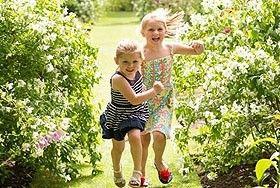 two children running in a garden