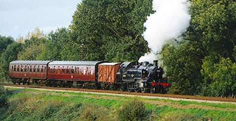 An old steam train drives through the country side