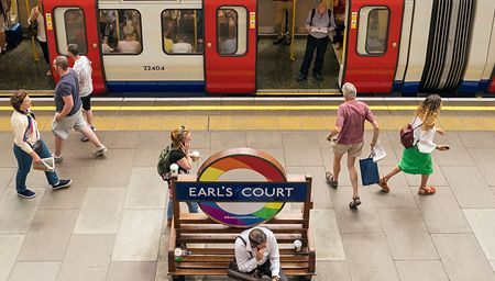 A platform with people at Earls Court Tube Station with a rainbow tube sign.