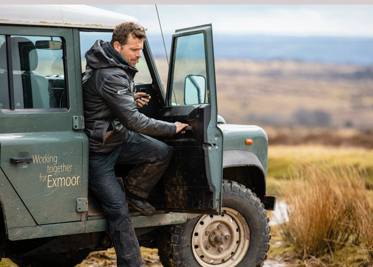 A man getting out of a jeep with Exmoor National Park on the side