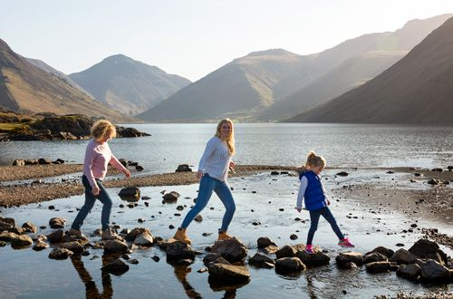 Three generations of women in a family (grandmother, mother and daughter) stepping playfully on rocks across the Wastwater lake.