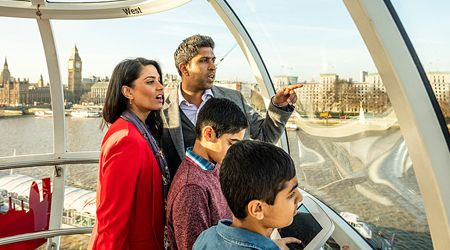 A man and a woman with two young boys sight see from the top of The London Eye