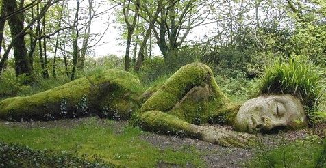 A statue of a woman laid sunken in the grass in a forest
