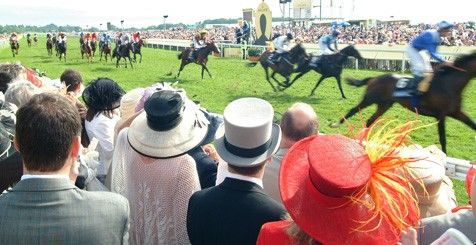 A crowd of people in hats watch a horse race