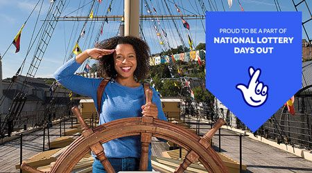 """A smiling woman saluting on an old-fashioned ship with rigging, and the National Lottery logo with """"Proud to be part of the National Lottery Days Out"""" on it."""