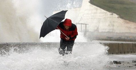 A person struggling with an umbrella in a storm