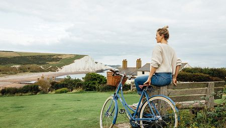 Rear view of woman sitting on bench near Coastguard Cottages, with white cliffs in the background, Seaford, East Sussex.