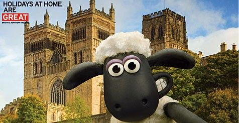 Children's TV character Shaun the sheep stands smiling in front of a cathedral. the text 'Holidays at home are great' features in the top left corner