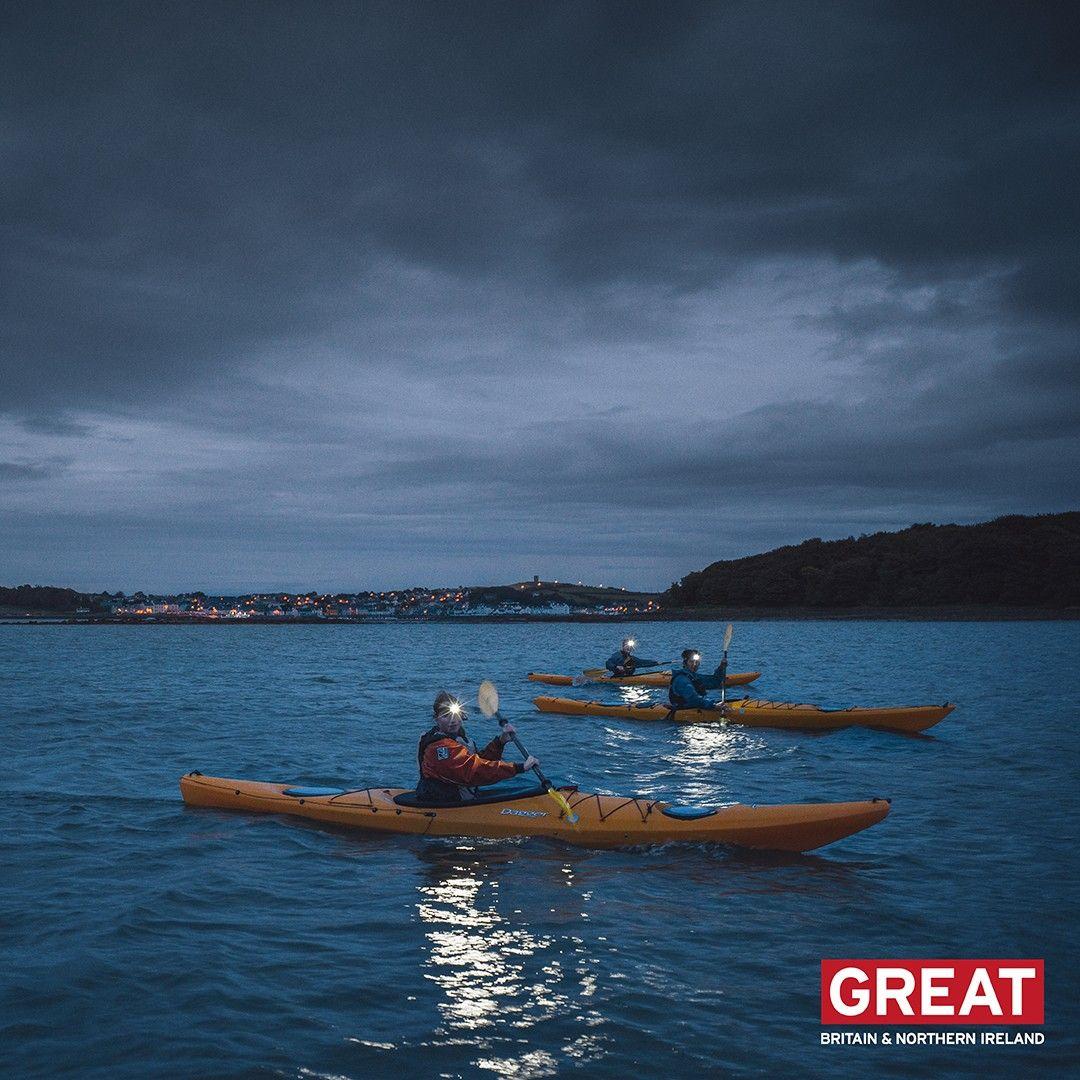 Three people kayak at night in the sea