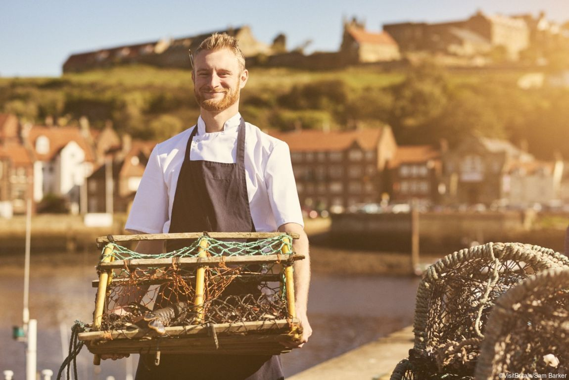 Chef holding lobster pot by the coast in Yorkshire