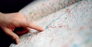 A hand points to a location on a road map