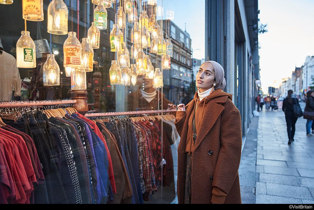 Girl window shopping standing on the street looking into a shop