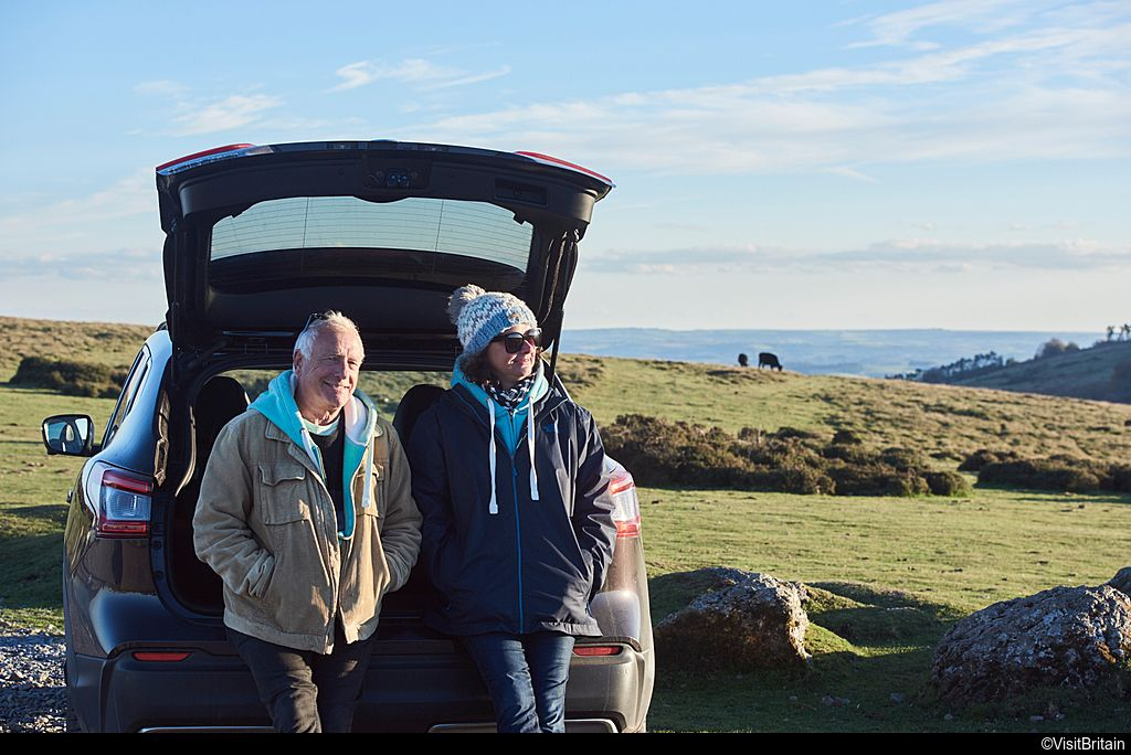 Man and woman standing next to open boot of car in Dartmoor National Park, Devon, England at sunset.