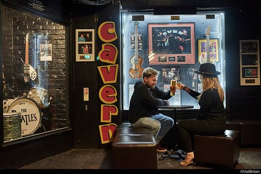 A smiling young couple raising their glasses in front of a display of Beatles memorabilia inside Liverpool's Cavern Club.