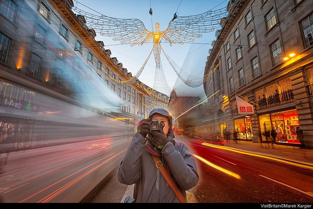 A woman taking a picture on regent street under the Christmas lights