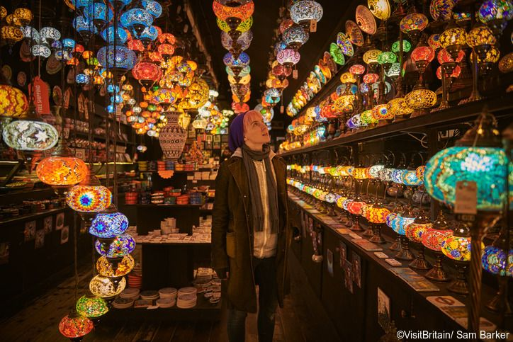 Image of a young woman admiring colourful lights and lamps in a lighting shop in Camden markets