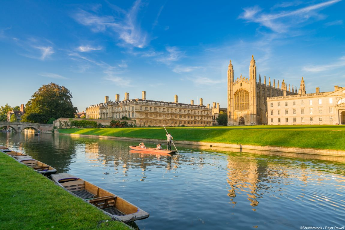 View of college in Cambridge with people punting on River Cam