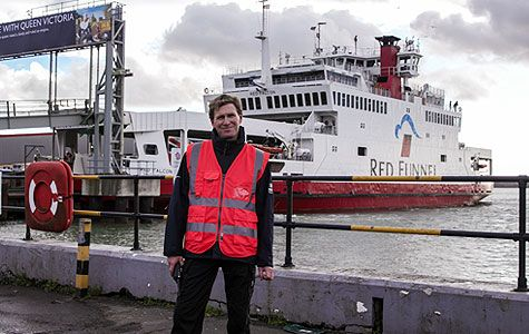 A man. Jim O'Reilly, stands in front of a large white ferry with the words Red Funnel on the side, wearing a red high-visibility vest