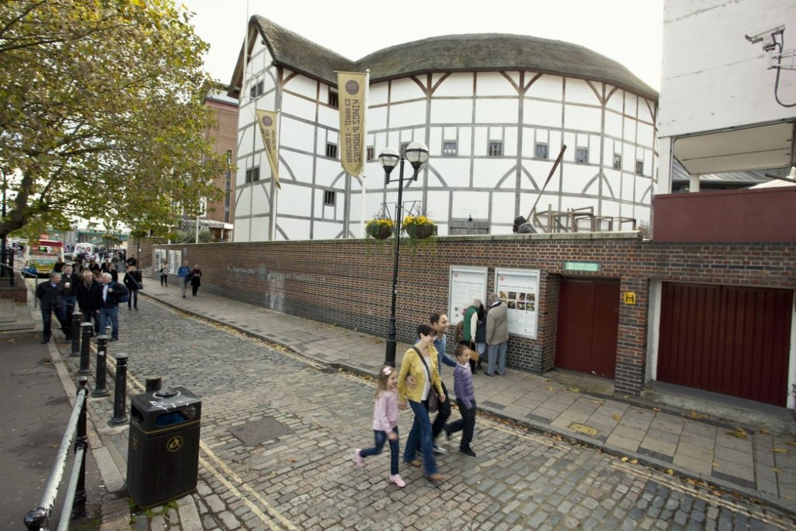 Family with two children walking past the Globe Theatre