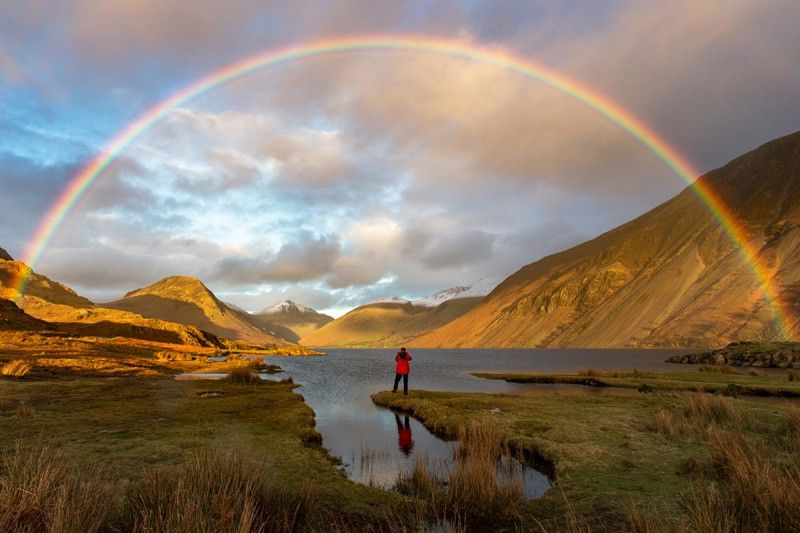 A man standing in a valley of lakes and mountains looking at a rainbow in the sky. Photographer: Mark Gilligan