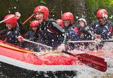 White water rafting, Canolfan Tryweryn, National White Water Centre, Wales. Group of people wearing wet-suits and red helmets paddling down a rapid.