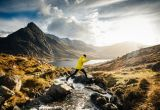 A man jumping across a stream making an ascent of Pen yr Ole Wen, Snowdonia, Wales