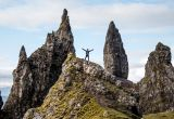 Man standing at basalt pinnacles called The Old Man Of Storr on the Trotternish Peninsula overlooking the Sound of Raasay, Isle of Skye, Scotland, UK.