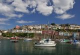 Rows of colourful houses overlook boats in Brixham harbour