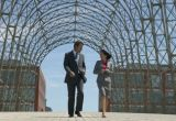 A man and woman in business suits walk under glass arched building