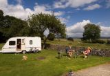 A couple sit on decks chairs outside their caravan in a field