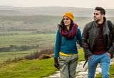 Young couple hiking in the Peak District National Park, Derbyshire, walking along a paved footpath